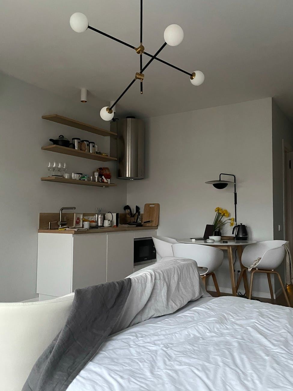 stylish interior of studio apartment with unmade bed