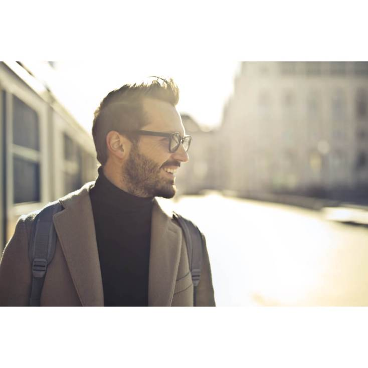 How to Develop Better Self-Esteem | A middle-aged man wearing a coat stands on the street and is looking in the opposite direction with a smile & satisfaction on his face