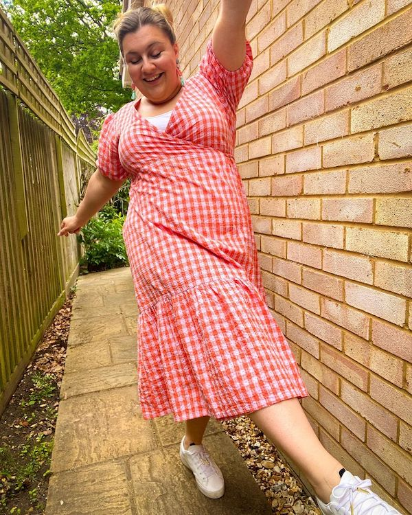 How to refresh your wardrobe without spending any money: Cat Brant wearing a red and pink gingham midi dress and trainers with her hands up in the air.