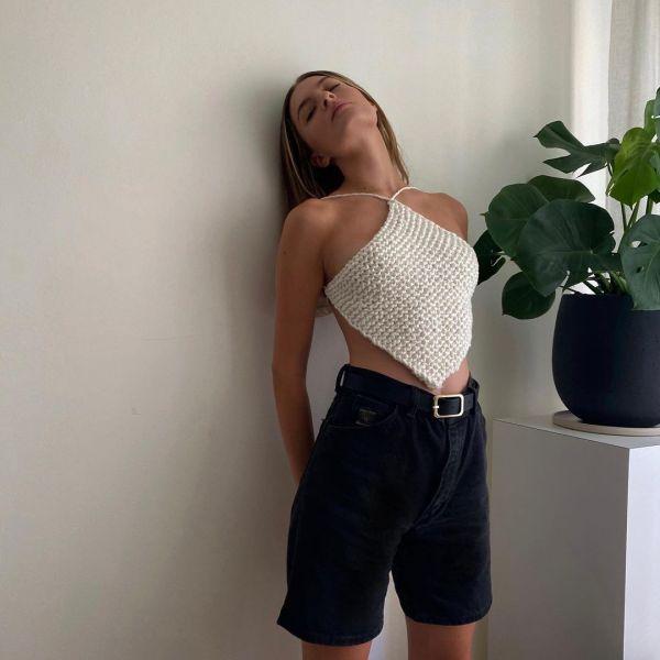 Influencer @nycbambi wearing black denim bermuda shorts and a crochet halterneck top