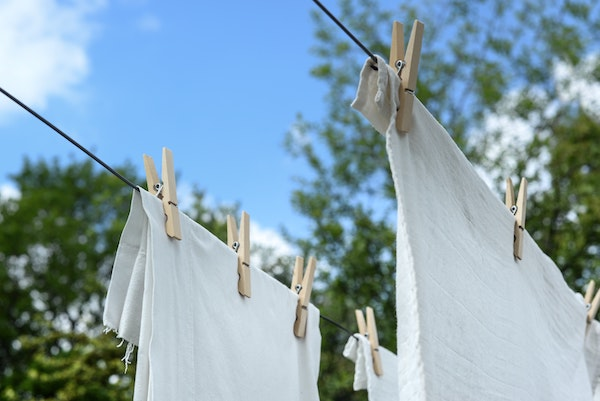 white tea towels and laundry hanging up on a washing line