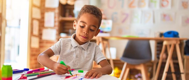 black toddler drawing using paper and marker pen in preschool