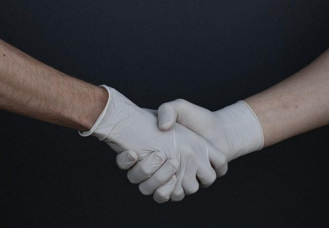 two hands shaking in white latex gloves