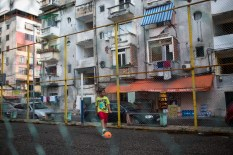 A young boy practices football in the little play area in the center of my block of apartment buildings.