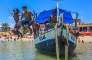 Children playing on boats on Jacuipe Beach.