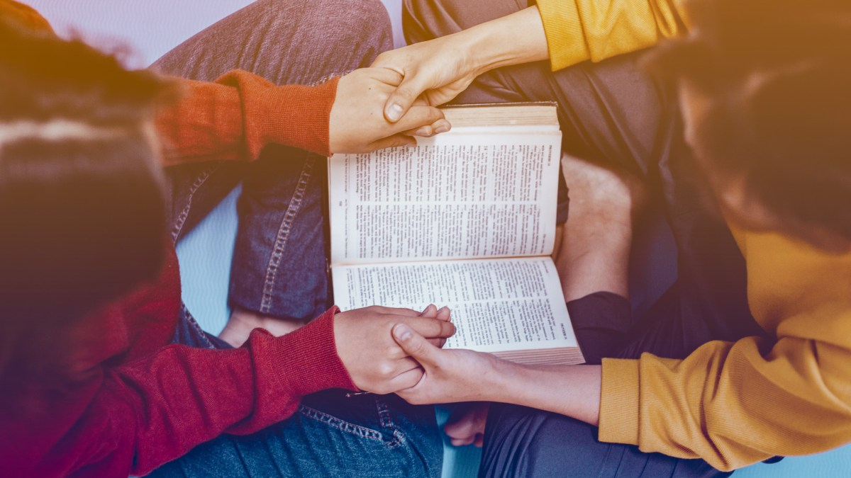 two young people hold hands across an open bible as if praying.