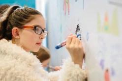 A girl drawing a cartoon face.