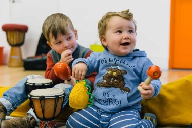 Two toddlers smiling. One boy is holding two maracas.