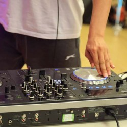 A close up of a boy's hand using a mixing desk