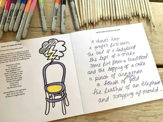 A spread of one of darts' Creative Directions doodle books. One page has a drawing of a grey chair with a yellow seat. The chair has a storm cloud above it with a yellow lightening bolt. The other page is filled with a handwritten spell. There are pens and pencils on the table above the book.