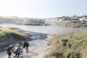 Artist Liz Crow, assisted by the production team, heads down the slipway at Shirehampton, Bristol, to dig the mud