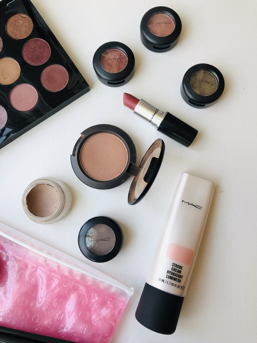 Flatlay of MAC products including blushes, lipsticks, creams, eyeshadows & primers