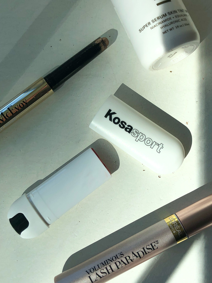 Kosas Lipfuel Hyaluronic Lip Balm posed with other beauty products