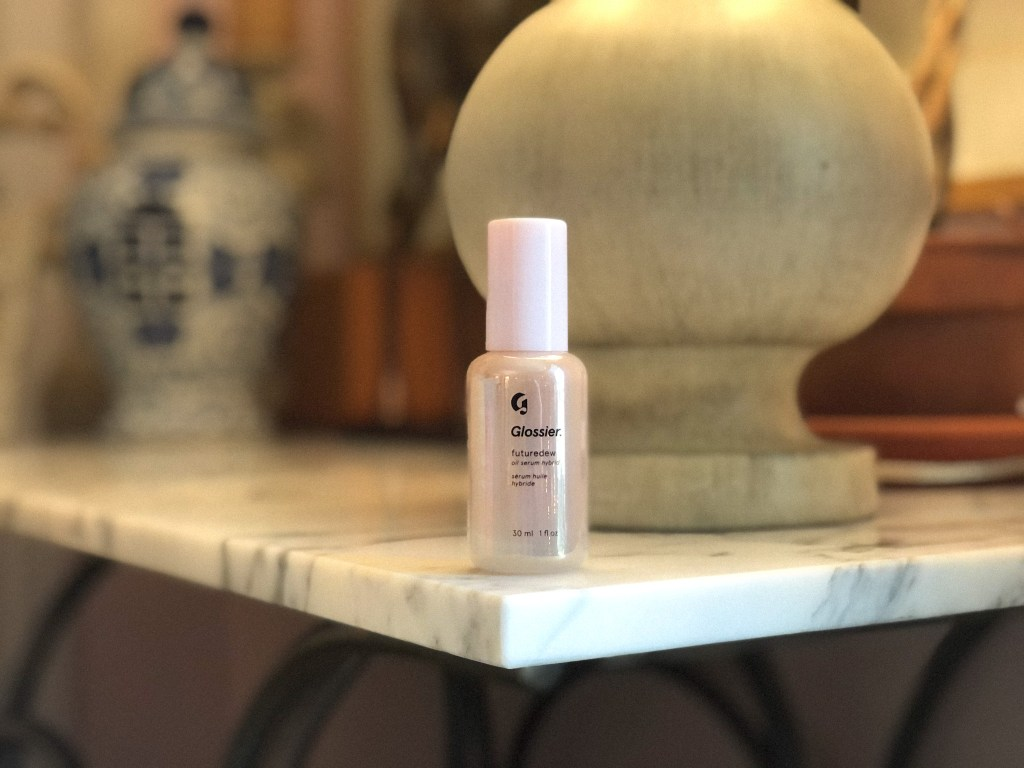 Glossier Futuredew bottle posed on marble table