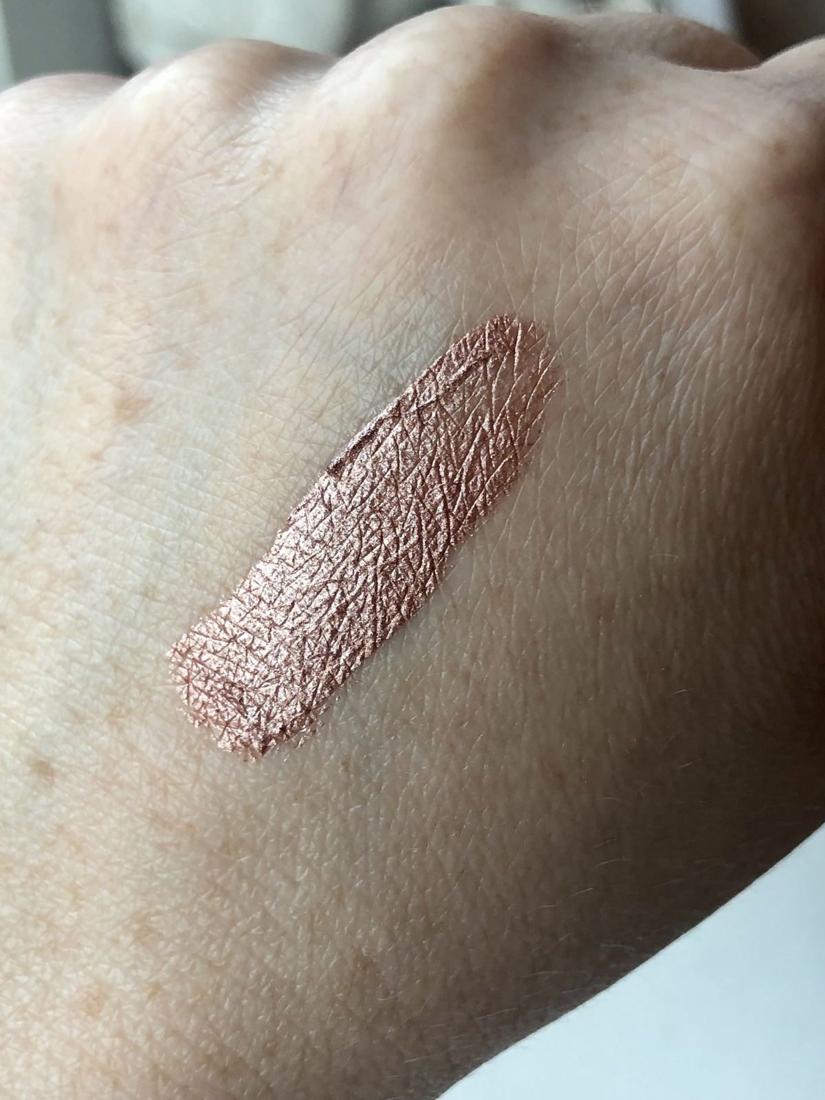 Swatch of liquid eyeshadow in the shade Rose Gold