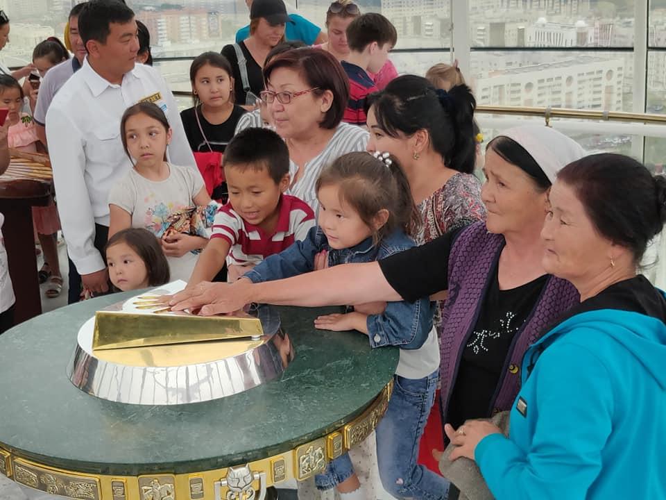 Tutti in fila per toccare il calco della mano del presidente kazako Nazarbaev sulla cima della torre bayterek