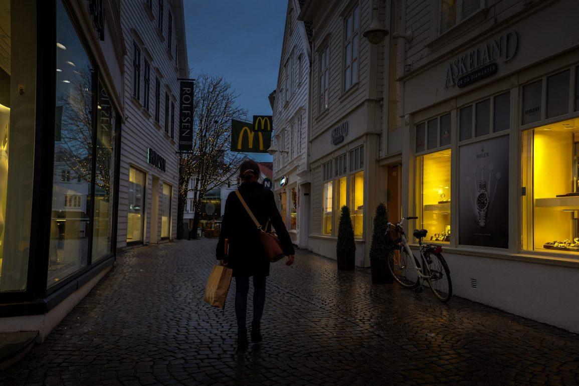 A woman walking on a street alone in the dark