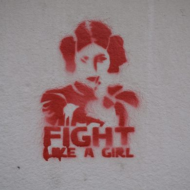 """An illustration of a girl with """"Fight like a girl"""" written under"""