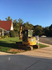 Backhoe being placed for more digging to find the sanitary line.