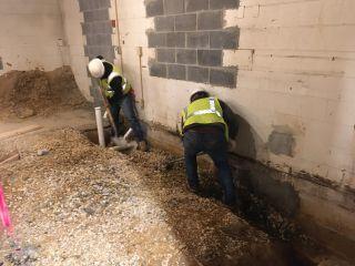 Plumbing crew in last excavation of kitchen.