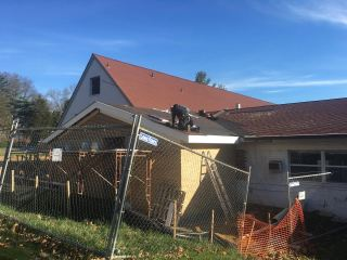Roofers add shingles to the new addition.