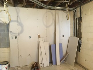 Drywalling in the coffee prep area. Note that the electrical panel has been removed.