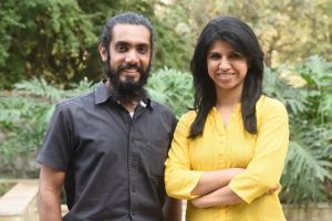 Aarti (dressed in yellow) standing smiling next to a bearded man dressed in black