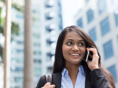 Closeup Portrait of an Indian businesswoman standing outside Mumbai modern office building using mobile phone