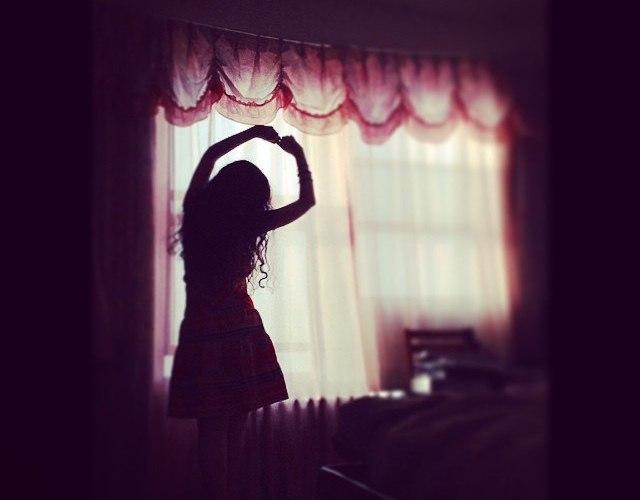 Een dansende vrouw in haar kamer