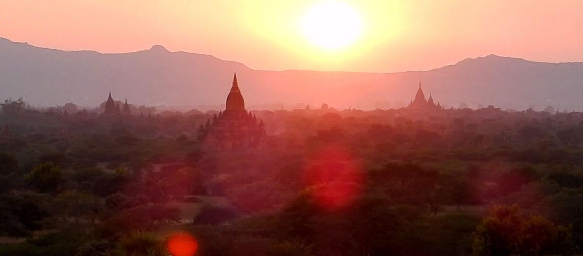 Zonsondergang over tempelstad Bagan, met een boer en koeien op de achtergrond