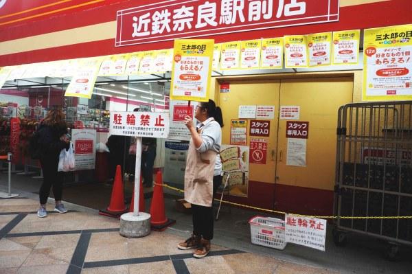 Winkelmedewerkster draagt een reclame bord in Japan