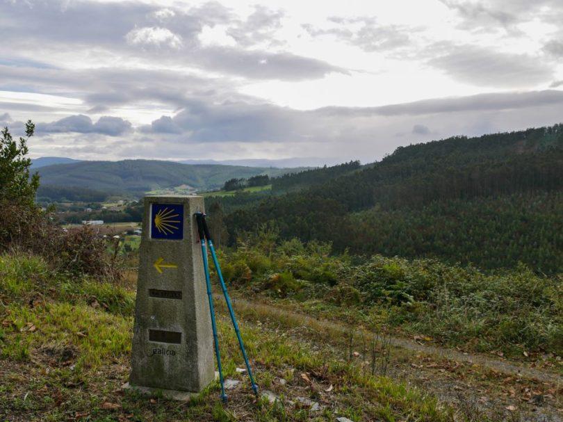 Een Camino pijl met uizicht over de bergen