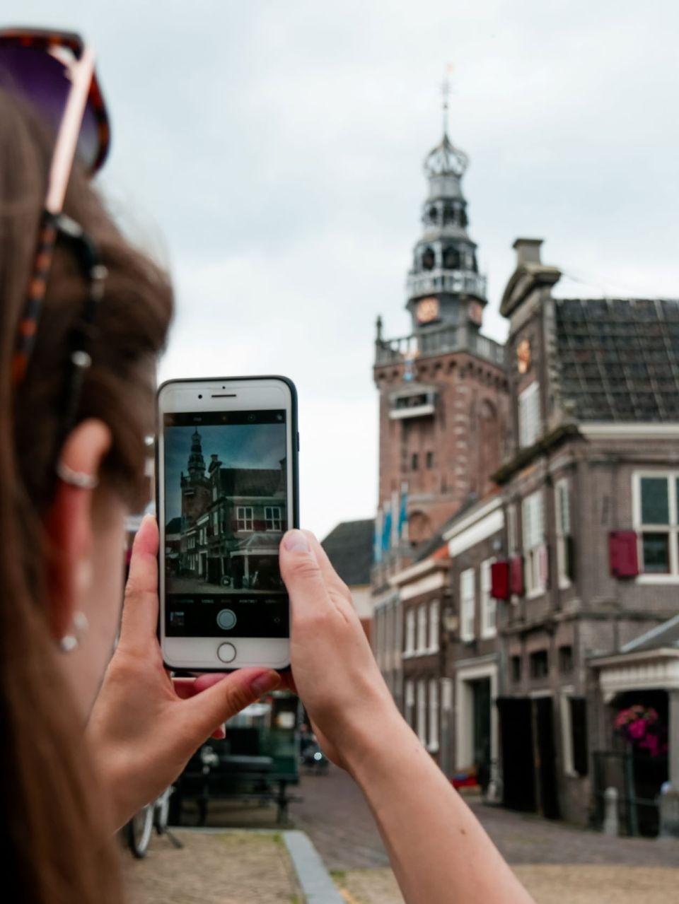 Femke zet met haar telefoon de kerktoren in Monnickendam op de foto