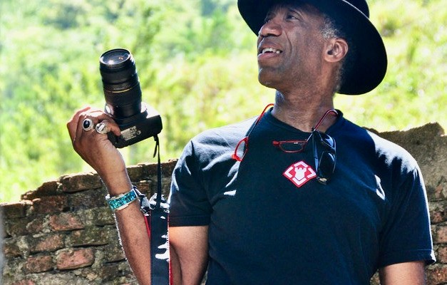 Kimo Williams smiling and holding a camera as he stands behind a lush, forested background.