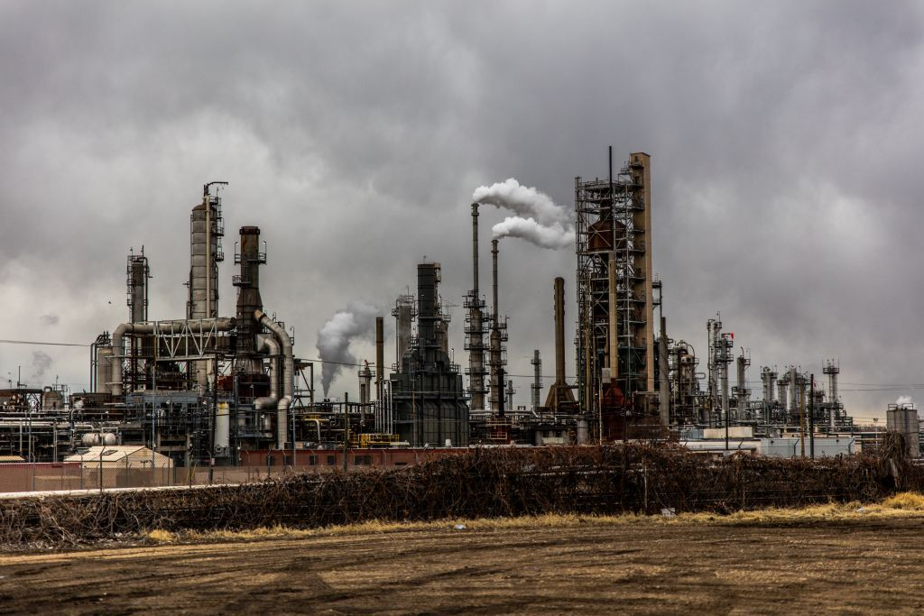 a refinery with towers and smokestacks belching smoke surrounded by a dreary, overcast, flat landscape.