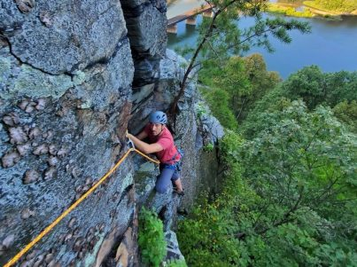 A man in climbing gear scales the side of a cliff face