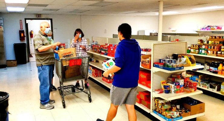 Two volunteers at Jefferson County Community Ministries collect groceries for a pick-up order.