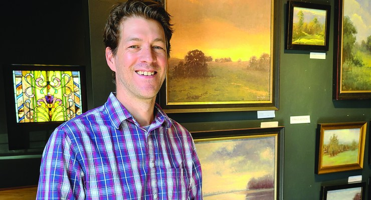 Artist Tim Clayton stands and smiles in front of a well on which his oil paintings are displayed.