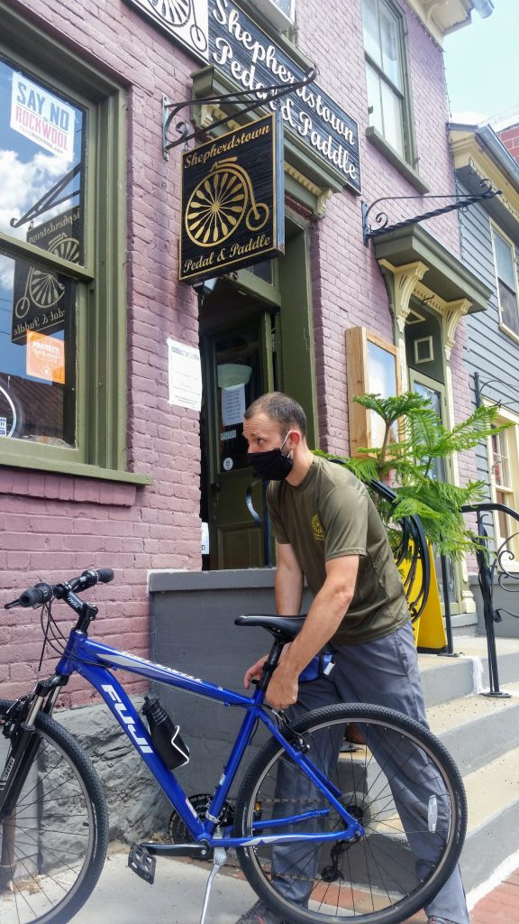 An employee of the Peddle and paddle bike shop repairs a bike outside the Peddle and Paddle shop in Shepherdstown.