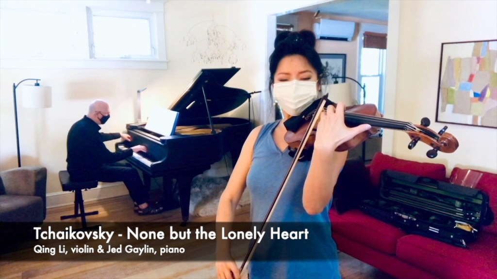two musicians play Tchaikovsky None but the Lonely Heart on piano and violin over a video stream.