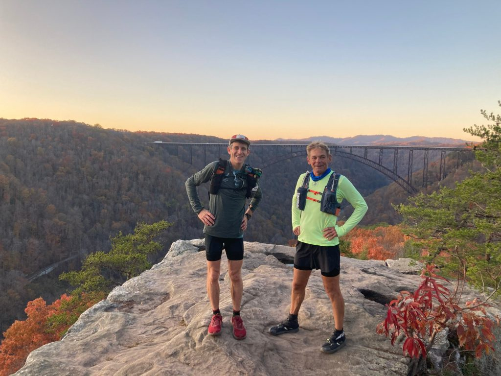 Dr. Mark Cucuzzella and James Munnis stand atop a rocky outcrop during a hike.