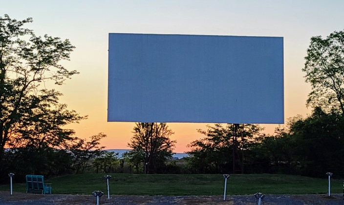 An outdoor movie screen at dusk as the sun sets in the background.
