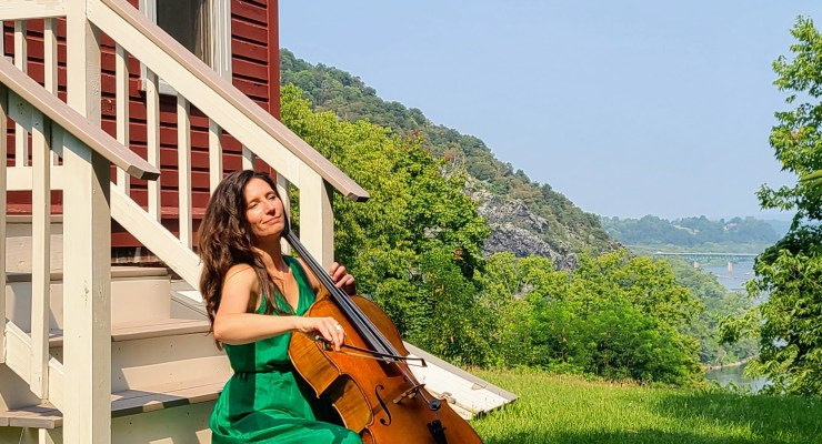 Katie Tertell plays a cello outside on the steps of a cabin in Harpers Ferry.