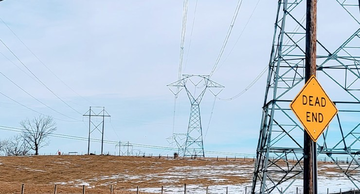 """electrical power lines stretch in to the distance while a """"dead end"""" sign is visible in the foreground."""