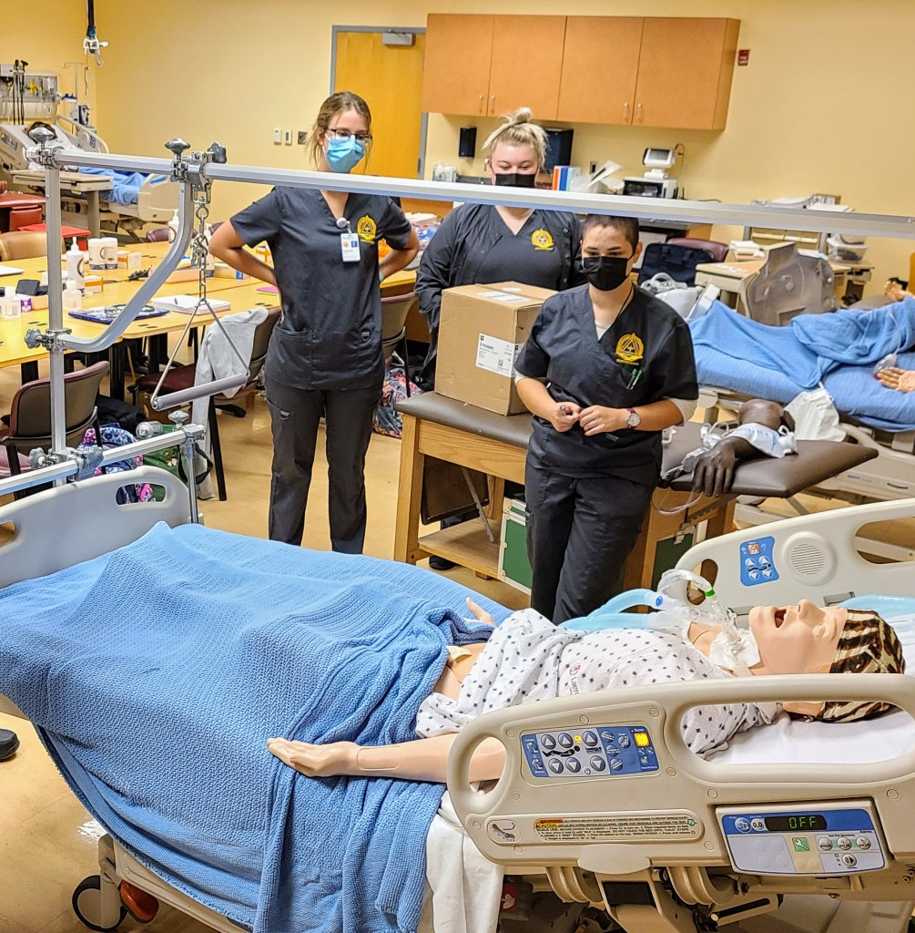 Nursing students practicing patient care with a manikin.