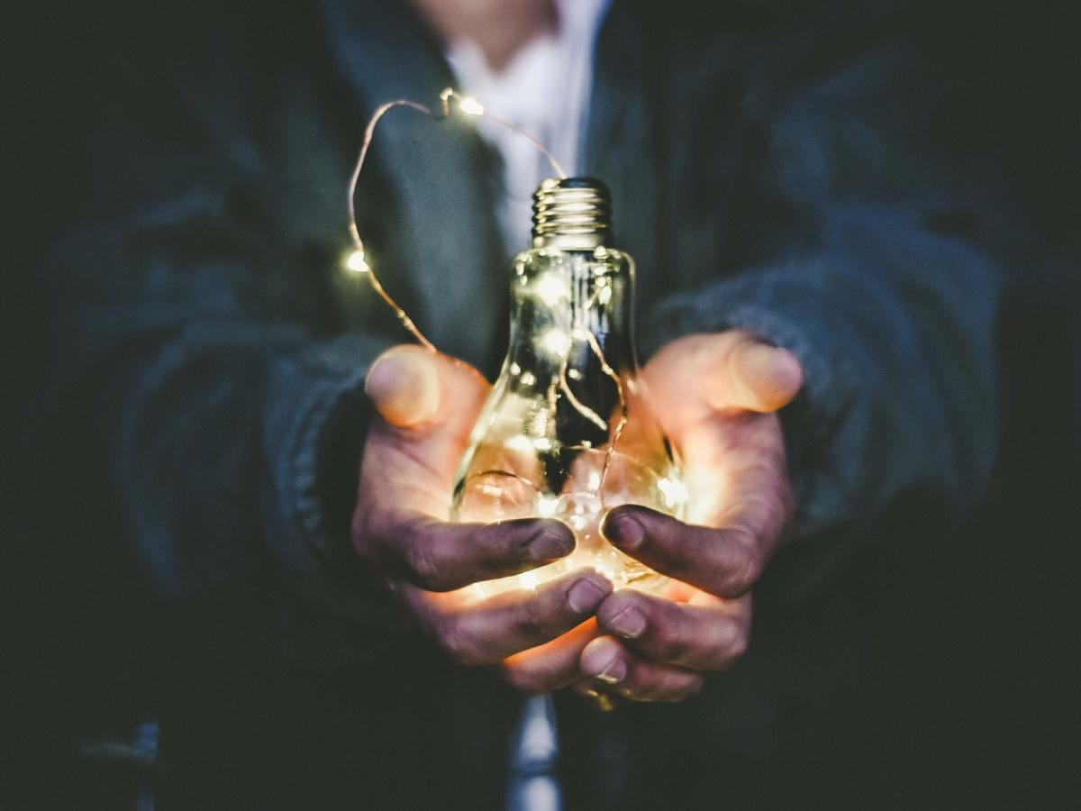 A light bulb in hands representing energy levels