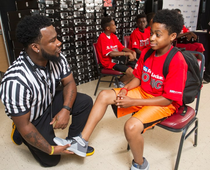 Kids Foot Locker striper Javon Hampton helps Ameer Holman, 11, of Cleveland, fit his Nike Kyrie II signature  shoes, Saturday, July 9, 2016, in Independence, Ohio. Kids Foot Locker donated 190 pairs of sneakers to Boys & Girls Clubs of Cleveland, to match Cleveland Cavaliers star Kyrie Irving's 190 points scored during the NBA championship series.  (Phil Long/AP Images for Kids Foot Locker)