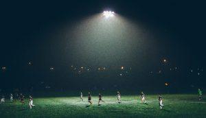 soccer players under stadium lights
