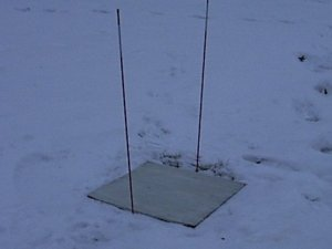 white board on the snow with stakes on either side