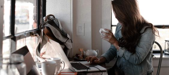 Woman using laptop while drinking cofee